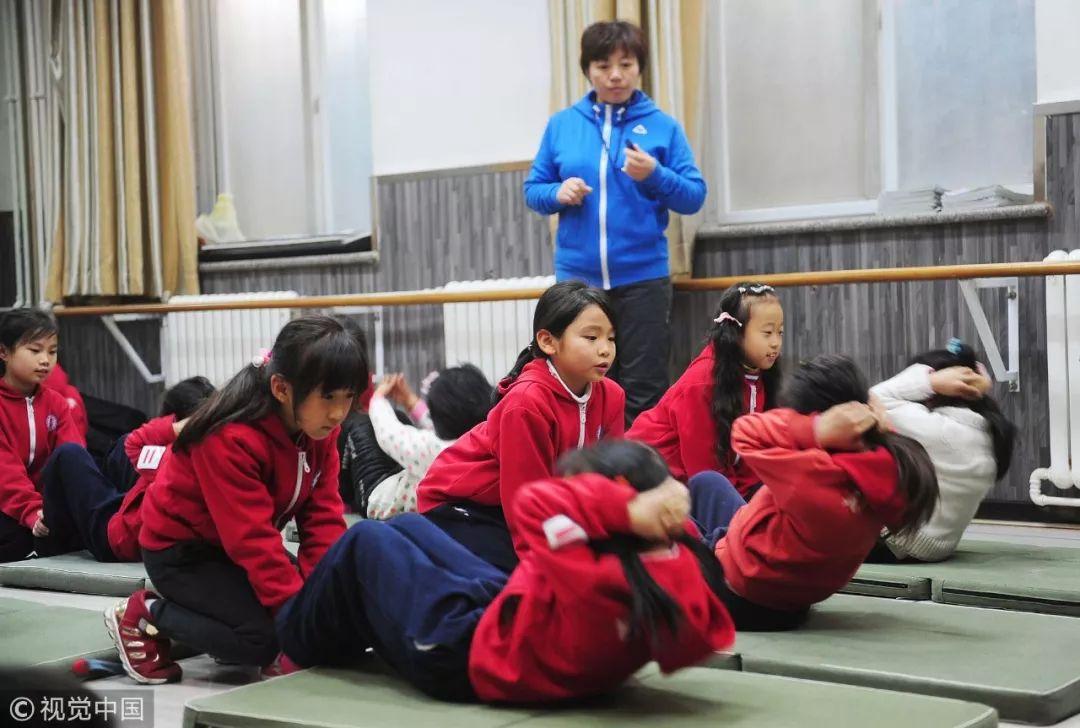 2015年11月30日,北京艺美小学形体室内,学生正在进行仰卧起坐等适合室内运动的项目 / 视觉中国