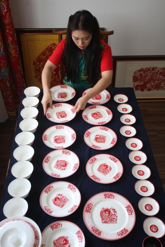 8月3日,梁巧燕在工作室检查新研发的剪纸餐具.