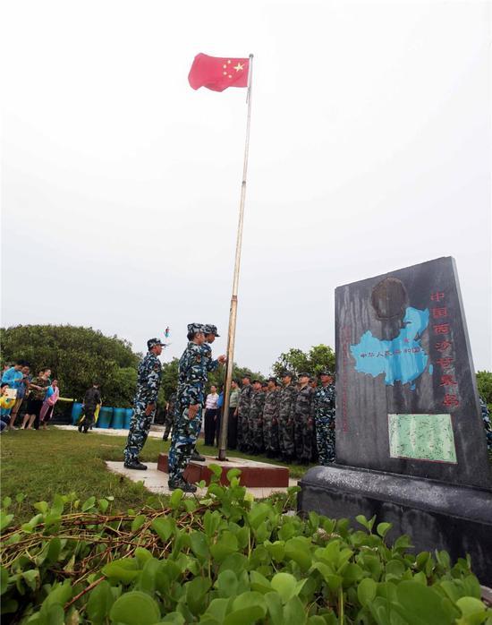三沙民兵在甘泉岛升国旗。周晓刚摄。