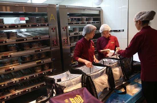 """3月17日,工作人员在""""盒马外卖""""的中央厨房分配即将外送的订餐。新华社记者 裴鑫 摄"""