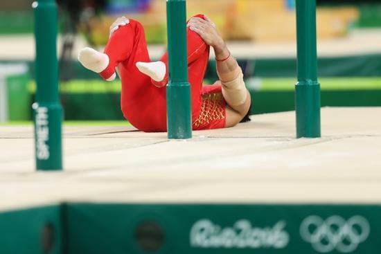 中国选手尤浩在比赛中落地动作失误。 当日,2016年里约奥运会体操男子双杠决赛在巴西里约热内卢举行,中国选手尤浩名列第八名。 新华社记者戚恒摄