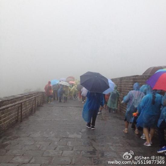 今晨,长城降雨,路面湿滑,游客打伞行走。来源@网友