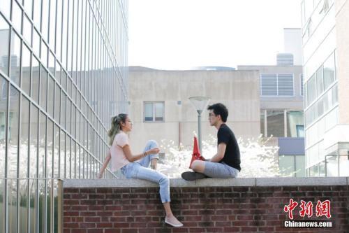 当地时间4月14日,美国费城宾夕法尼亚大学校园,学生在春花灿烂的校园中。 中新社记者 ?#38395;?摄