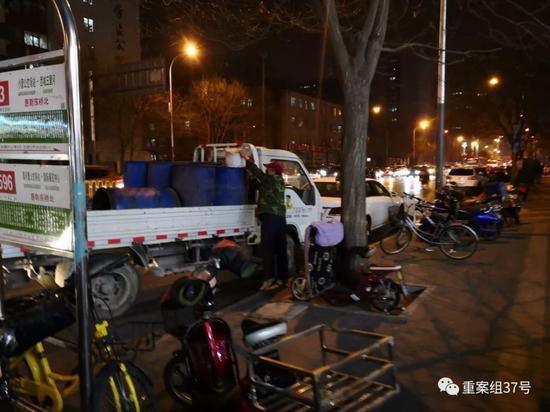 ▲3月22日,朝阳区小营路,一辆泔水车停靠在公交站旁,拉运泔水的人从宏状元每次搬运两桶泔水倒入车内泔水桶内。    新京报记者 王飞 摄