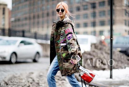 韩国模特Irene Kim身穿莫杰 (Marc Jacobs) 贴花迷彩外套搭配不规则设计牛仔裤和菲利林3.1 (3.1 Phillip Lim) 短靴,手拎香奈儿 (Chanel) 水桶包街拍
