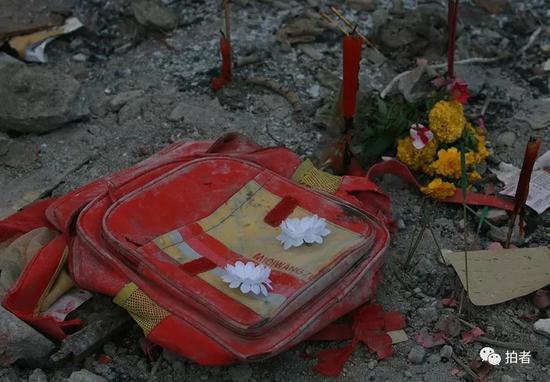 2008年5月19日,都江堰新建小学,遗落的书包上放着悼念的小白花。摄影/何龙盛