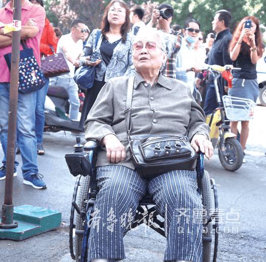 一名78岁的老人自己坐轮椅来到省实验中学考点,看着自己的孙子进考场。