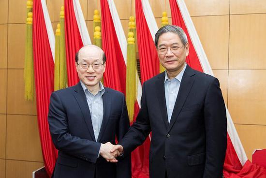 图为刘结一与张志军(右)握手。