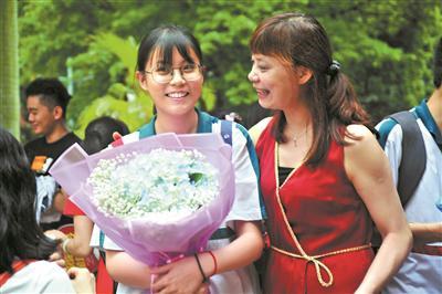 在广雅中学考点,有家长给完成第一天考试的女儿送上鲜花,并在考点门口留影。广州日报全媒体记者 李波 摄