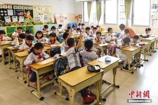 资料图:小学生放学后在特定的托管教室内做作业。中新社记者 陈骥旻 摄