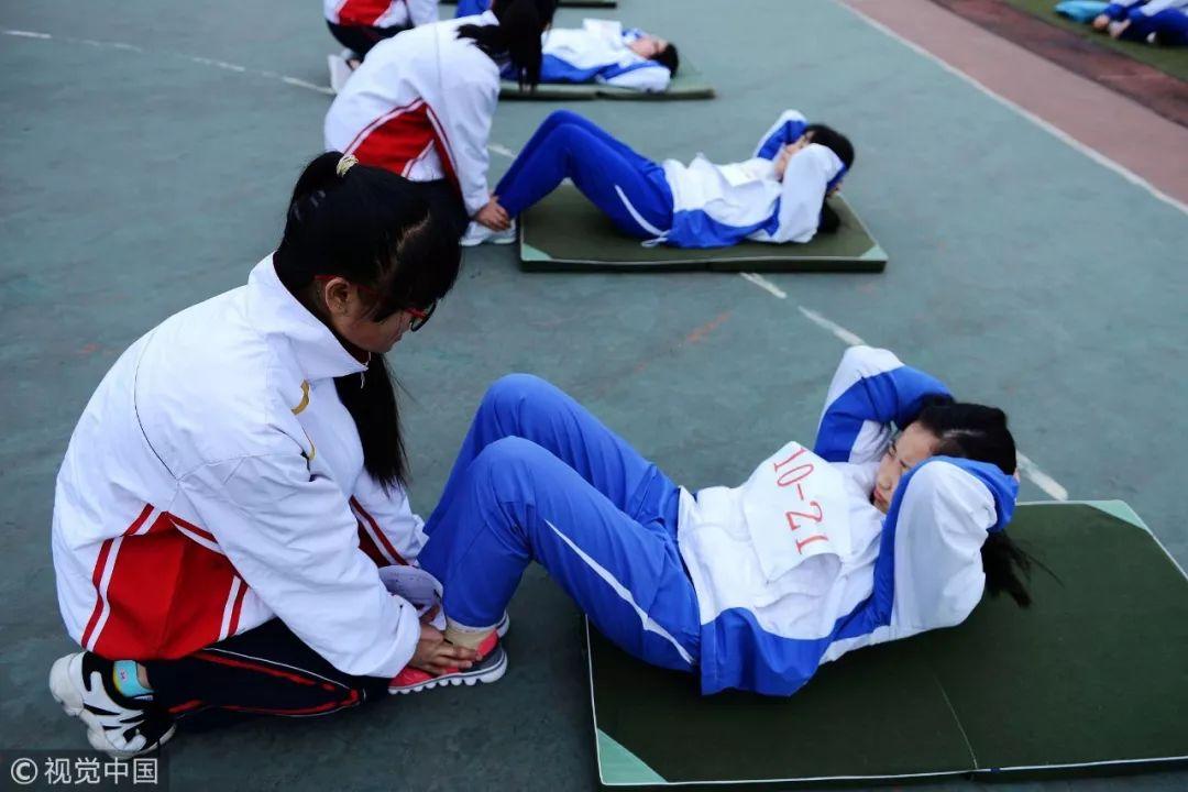 2016年4月20日,山东省青岛开发区职业中专考场,参加体育中考的考生在进行仰卧起坐考核 / 视觉中国