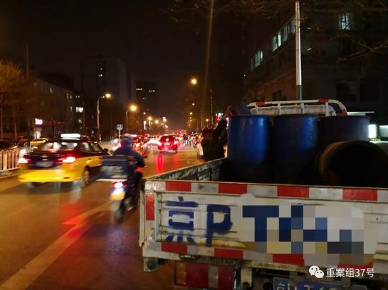 ▲3月22日,朝阳区小营路,一辆泔水车旁,拉运泔水的人从宏状元搬运泔水倒入车内泔水桶内。  新京报记者 王飞 摄