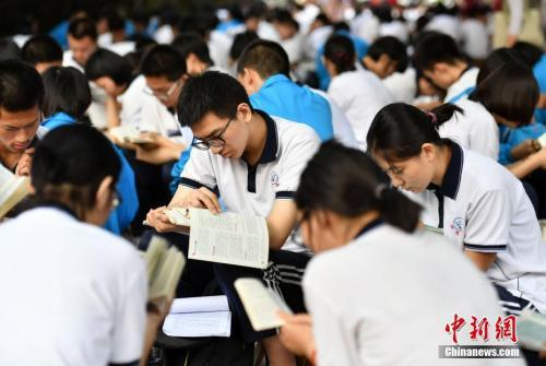 6月7日清晨,河北石家庄一高考点附近,参加高考的学生们利用进入考场前的时间看书复习。
