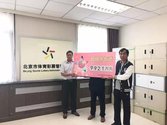 北京体彩中心工作人员与大奖得主(中)合影