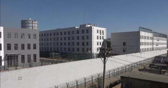 """组成监狱""""大包围""""的白色围墙有6米多高,墙上边是1米多高的电网。新京报记者孙旗摄"""
