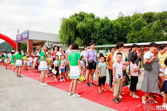 当天早上,大批新生和家长一起走过红地毯进入校园,这种贵宾级的待遇让许多家长非常开心,纷纷拿出相机拍照留影。