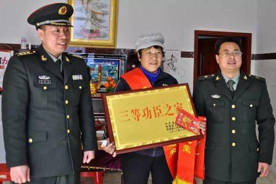 """▲金溪籍军人杨凯的母亲,喜捧""""三等功臣之家""""牌匾。"""