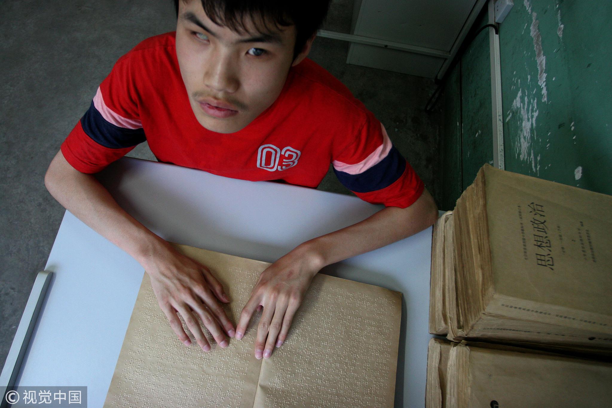 2007年5月,河南郑州,盲人高考班,一名盲人学生正在阅读盲人课本。/视觉中国