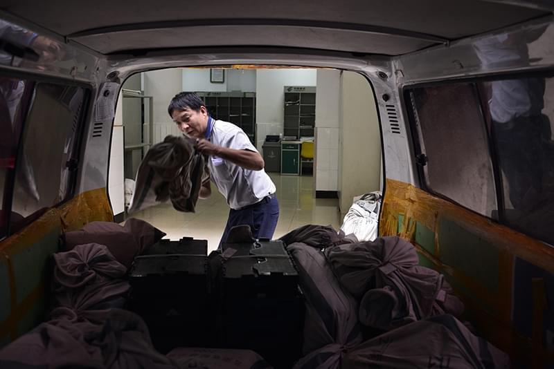2012年09月27日,云南省昆明市,中国邮政金实投递支局门口,清晨送报纸和信件包裹等的邮政车。沉重的货物常常让这些师傅们挥汗如雨。