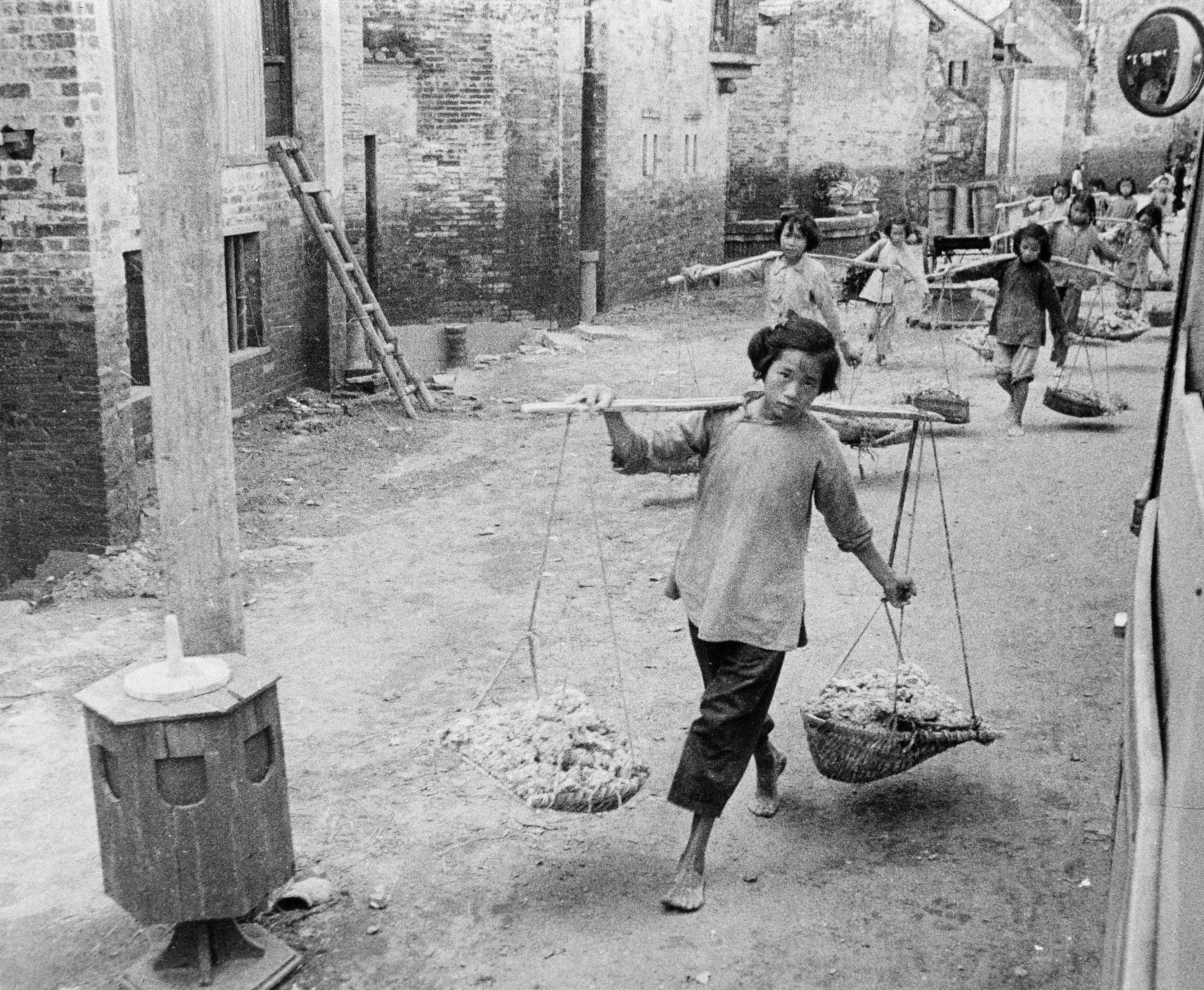 1961年4月,中国大跃进时期,一名放学后干活的女孩。/AP