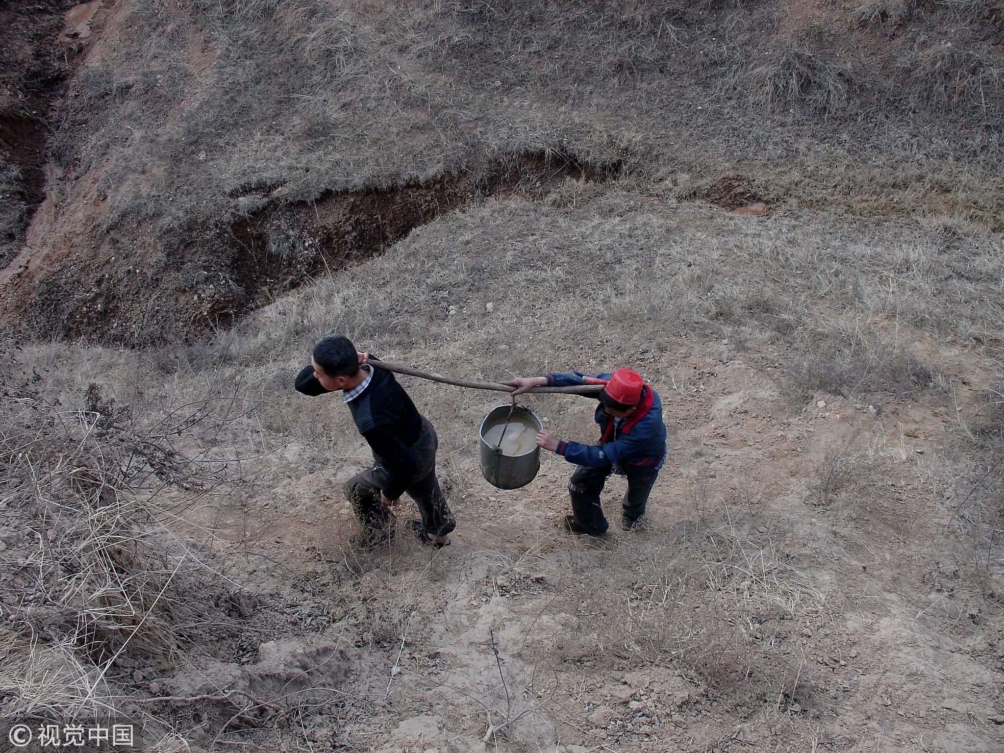 甘肃省正宁县榆林子,两位中学生从山下吃力的抬水上山。 / 视觉中国