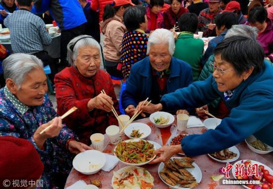 """资料图:北京一乡村老人正在开心地同吃""""重阳节和睦百家宴""""。 图片来源:视觉中国"""