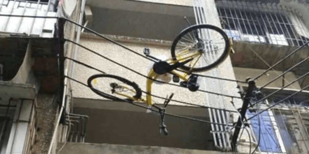 楼上丢下共享单车挂在高压线上 被恶意破坏