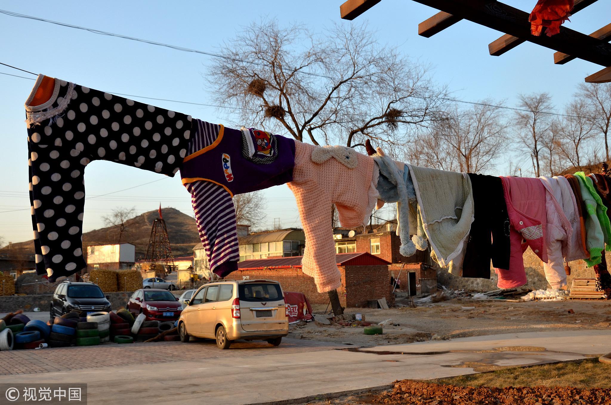 爱心村晾晒的孩子衣服,很多来自社会捐赠。/视觉中国