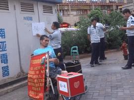 """南宁残疾男子卖唱屡被投诉 城管劝离不成举""""骗人""""牌"""