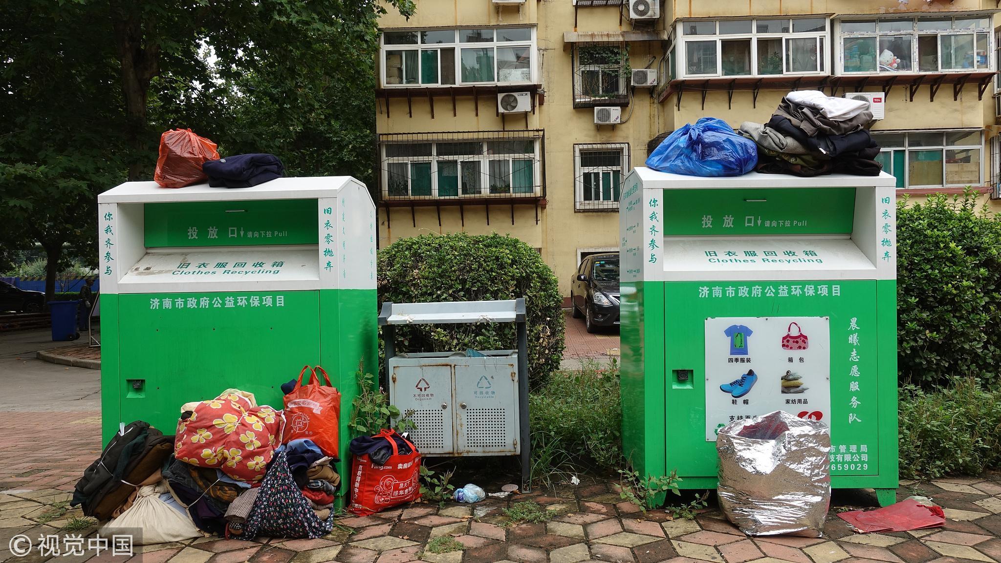 2017年8月18日,山东济南历城区济钢新村小区内的旧衣服回收箱,堆满了小区居民舍弃的旧衣物。/视觉中国