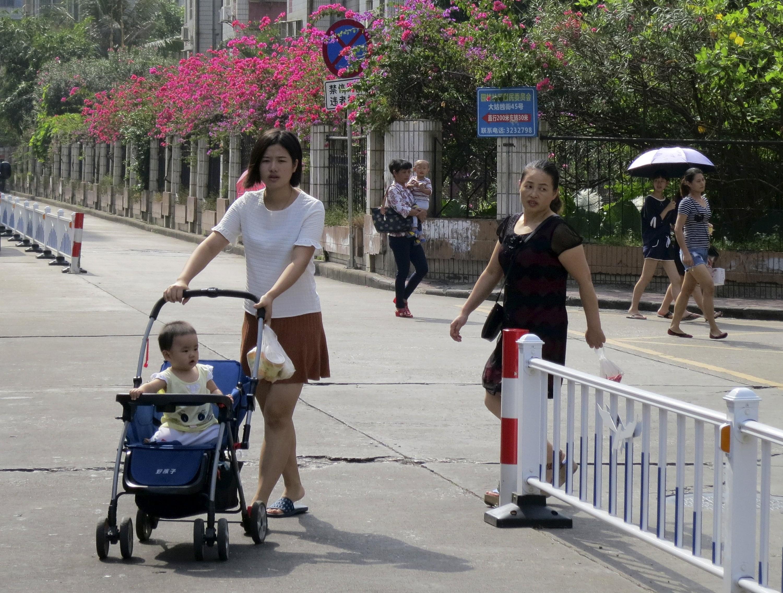 2015年10月30日,珠海,一位母亲推着女儿市场采购。/视觉中国