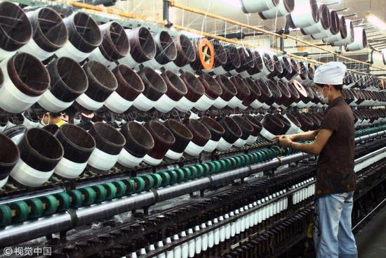 2013年6月19日,山东济宁一家玻纤企业的女工正在作业/视觉中国