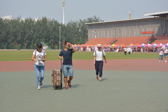 2016年9月10日,河北邯郸。参与迎新的学长替学妹提行李箱。男多女少的情况下,更多学长会把学妹当做追求目标,成为你的竞争对手/视觉中国