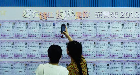 2018年7月7日,人们在杭州的相亲大会上查看观看相亲资料。相亲很像是相互筛选简历,这样条件虽然能匹配,但往往省略了情侣间相互了解的过程/视觉中国