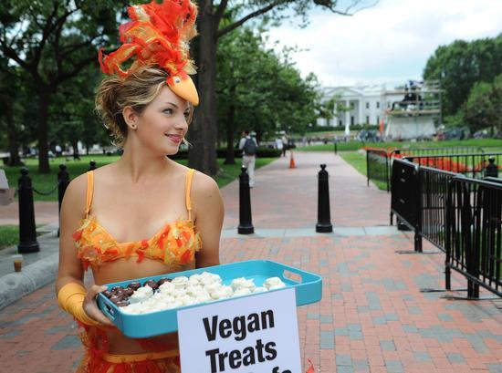 """2010年8月25日,美国华盛顿,善待动物组织成员向人们分发没有鸡蛋的纸杯蛋糕,以警示 """"沙门氏菌""""感染,提倡食素食,但其实工业饲养中沙门氏菌的感染率很低/视觉中国"""