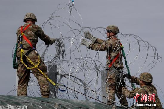 资料图:美国士兵在美墨边境安装铁丝网严防移民入境