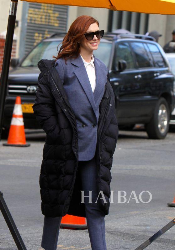 2018年12月04日,安妮·海瑟薇 (Anne Hathaway) 纽约街拍,身穿白色衬衫,搭配灰色西装套装,外搭黑色长款羽绒服