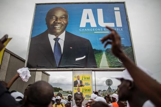 8月26日,让·平支持者在现任总统阿里·邦戈·翁丁巴竞选海报前集会。(新华/法新)