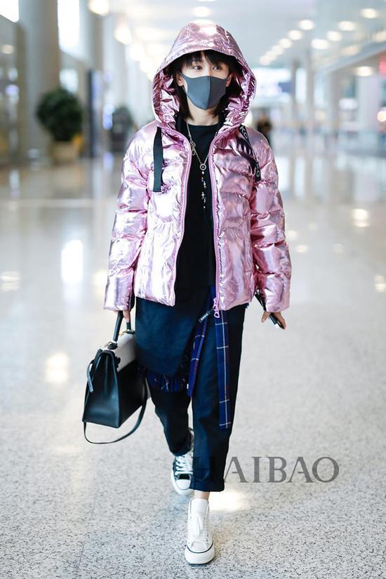 王子文2018年11月5日机场街拍:身着Pinko粉紫色羽绒服,搭配Sacai拼接黑T恤、拼接长裤,踩匡威 (Converse) 鸳鸯帆布鞋由上海前往北京