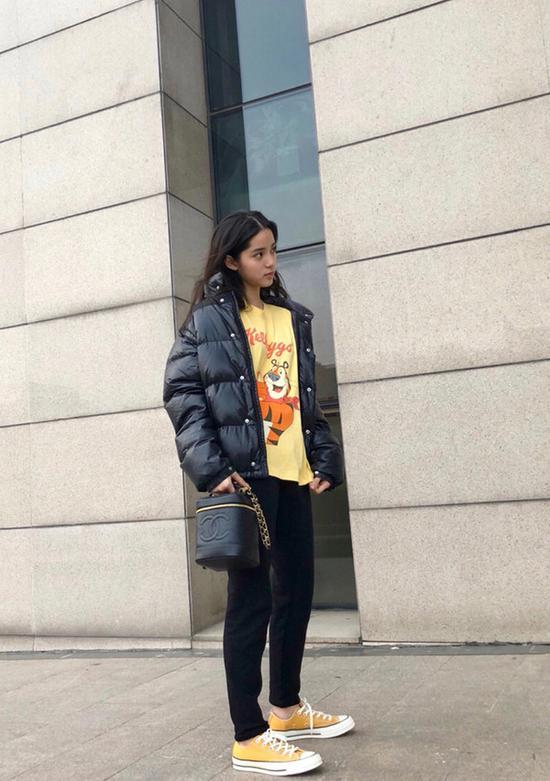 欧阳娜娜的私服Look:身着盟可睐 (Moncler) 羽绒服,搭配X2印花T恤,与优衣库 (Uniqlo) 黑裤,踩匡威 (Converse) 帆布鞋,拎香奈儿 (Chanel) 手袋