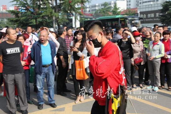 这位戴口罩的帅哥穿了一件宽松的红色外套