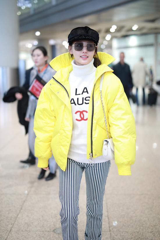 身穿Chanel白色高领毛衣,外搭明黄色羽绒服,搭配条纹裤,穿Gucci珍珠鞋,戴黑色报童帽