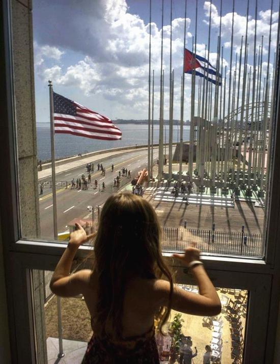 资料:2015年8月14日,古巴首都哈瓦那美国使馆内,一名女孩透过玻璃窗看着使馆外。(图片来源:新华/美联)