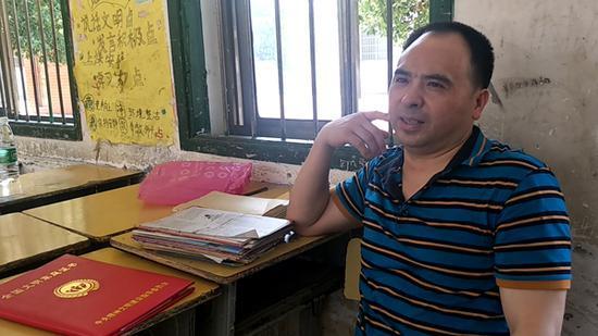 教师吴才有。 本文图片均为澎湃新闻记者 蒋格伟 图爬屋顶修漏雨教室摔残疾