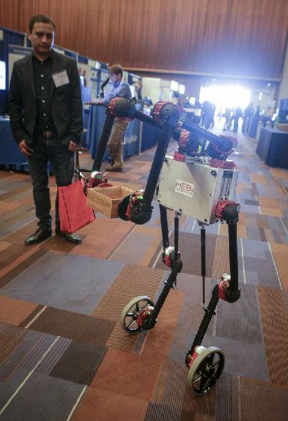 一个机器人示范搬运小木箱。(来源:新华社)