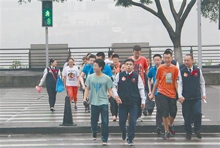 参加考核的学生在志愿者的陪同下过斑马线